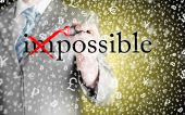 Businessman Hand turning the word Impossible into Possible with red marker — Stock Photo