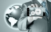 Businessman showing gears on smartphone — Stock Photo