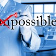 Businessman Hand turning the word Impossible into Possible with red marker — Stock Photo #64493481