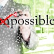 Businessman Hand turning the word Impossible into Possible with red marker — Stock Photo #64493491