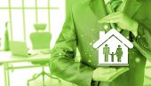 Businessman protecting family in home with hands — Stock Photo