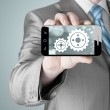 Businessman shows gears on smartphone — Stock Photo #66990183