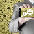 Businessman shows gears on smartphone — Stock Photo #66990239