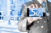 Businessman holding phone with 5G — Stock Photo