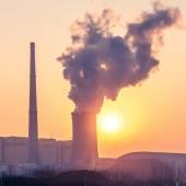Schoorsteen en koeltorens van elektriciteitscentrale tijdens zonsondergang — Stockfoto