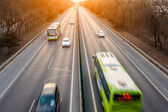 Cars in motion blur on street during sunset — Stock Photo