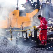 Workers making asphalt with shovels at road constructio — Stock Photo