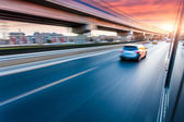 Car driving on freeway at sunset, motion blur — Stock Photo