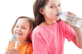 Little girls drinking mineral water — Stock Photo