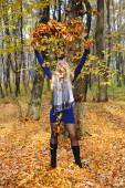 Beautiful happy woman playing with autumn leaves in forest — Stock Photo