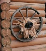 Old cart wheel against the background of a wooden wall — Foto Stock