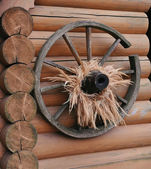 Old cart wheel against the background of a wooden wall — 图库照片