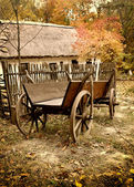 Vintage wooden cart in the yard in the autumn — Stock Photo