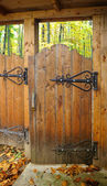 Ornate wooden gate with wrought iron hinges — Stock Photo