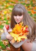 Portrait of beautiful young woman with autumn leaves — Stock Photo