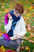 Beautiful girl with book in the autumn park — Stock Photo