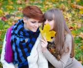 Young pretty girls whisper at the autumn park — Stock Photo