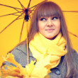 Beautiful young woman with a yellow umbrella — Stock Photo #56054649