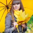 Beautiful young woman with a yellow umbrella — Stock Photo #56054751