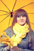 Schöne junge Frau mit einem gelben Schirm — Stockfoto
