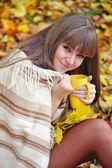 Giovane e bella donna che tiene la tazza di tè in mano su uno sfondo di foglie d'autunno — Foto Stock