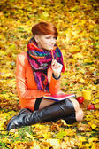 Red-haired student girl with notebook on a background autumn leaves — Zdjęcie stockowe