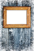 Old frame on snowbound wooden background — Stock Photo