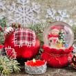 Christmas decorations of candles and snow globe with snowmen — Stock Photo #60885703