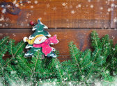 Branches of fir with snowman and Christmas decorations on wooden background — Stock Photo
