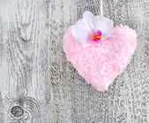 Fur pink heart with a flower orchid on wooden background — Stock Photo