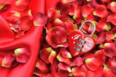 Padlock heart-shape on a background of red petals and satin — Stock Photo