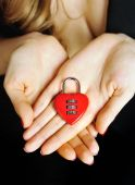 Padlock heart-shape in women's hands — Stock Photo