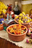 Healing herbs and tinctures in bottles on sackcloth, dried flowers, herbal medicine — Stok fotoğraf