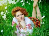 Young beautiful woman in the Ukrainian national costume in flowering meadow — Stock Photo