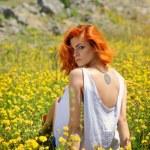 Beautiful young girl among yellow wildflowers — Stock Photo #77439930