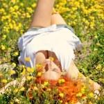 Beautiful happy girl lies among yellow wildflowers — Stock Photo #77439954