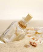 Summer sandy beach concept with letter in bottle — Stock Photo