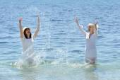 Two young smiling womans splashing water in sea — Stock Photo