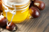 Jar of honey with organic chestnuts on a wooden table — Stock Photo