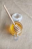 Honey jar isolated on jute background — Stock Photo