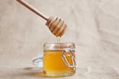 Honey drip with jar isolated on jute backgroun — Stock Photo