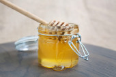 Honey drip with jar isolated on jute background — Stock Photo