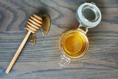 Honey dipper with honey on wood background. — Stock Photo