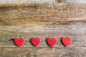 Four glitter hearts on reclaimed wood, valentines day background — Stock Photo