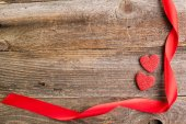Red glitter hearts with red satin ribbon on reclaimed wood, vale — Stock Photo