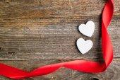 White glitter hearts with red satin ribbon on reclaimed wood, va — Stock Photo
