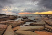 Sun rays, rocks and storm clouds — Stock Photo