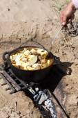 Meat with potatoes in a cauldron on fire — Stock Photo
