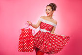 Happy Woman Holding Up Kidswear. Pin-Up Retro Style. — Stock Photo