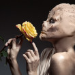 Beauty and the beast. Ugly witch with beautiful flower in hand. — Stock Photo #55373843